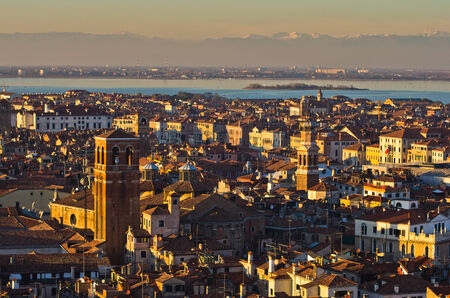 telephoto: Telephoto aerial view of sunset in Venice from Campanila bell tower at piazza San Marco, italian alps in background, Italy Stock Photo