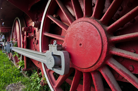 Red wheels of big old steam locomotive from Orient Express, in front of a factory where it has been produced photo