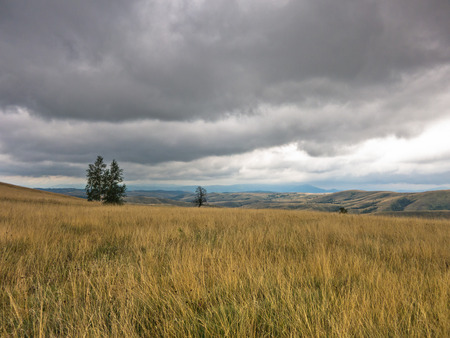 hillsides: Dark clouds of summer storm over the prairie path through hillsides with dry vegetation, central Serbia Stock Photo