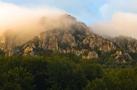 Rocky peaks at foggy sunrise, trekking path at Suva Planina mountain, east Serbia photo