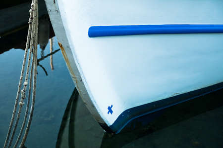 bow of boat: The bow of a white greek fishing boat with small blue cross in a harbor at morning, Sithonia, Greece Stock Photo