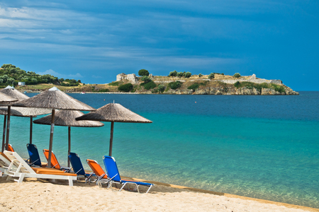 sunshades: Beachscape with orange chairs, straw sunshades, old roman fortress in a background, Sithonia, Greece