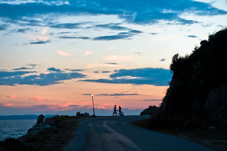 Young couple with tandem bicycle at greek sea coast after sunset, Sithonia, Greece