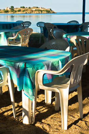 taverna: Tables of a restaurant, taverna, in shade of trees at Toroni beach in Sithonia, Greece