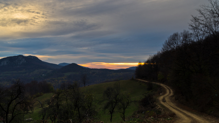 serbia landscape: Homolje mountains landscape with a winding gravel country road at sunset of an autumn sunny day, east Serbia