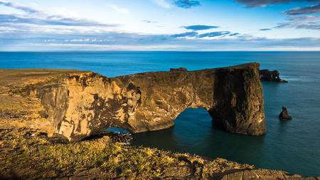 volcanic rock: Magnificent rock arch at Dyrholaey, Iceland. Dyrholaey means the hill island with the door hole. It is 120 m high and you are able to walk the arch or the bridge if you are not afraid.