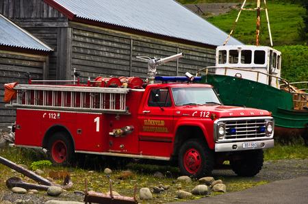 antique fire truck: SIGLUFJORDUR, ICELAND - SEPTEMBER 3, 2015: Red fire truck at Siglufjordur harbor, north Iceland