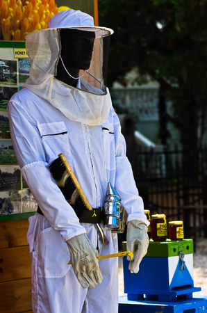 protective clothing: Beekeeper model with equipment and protective clothing, bee hives and honey products, Sithonia, Greece
