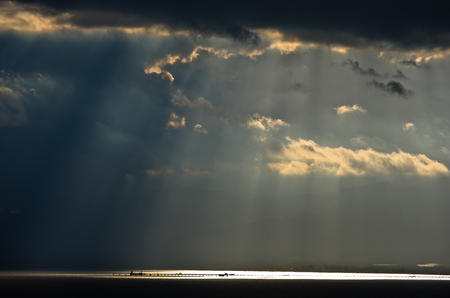 storm background: Divine light on a long pier after a sea storm, Sardinia, Italy