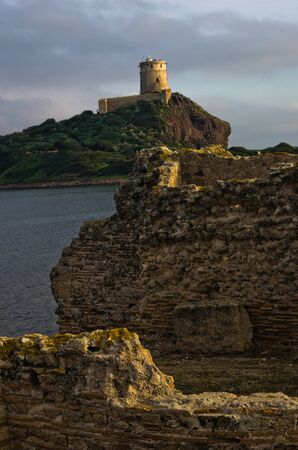 archeological: Tower Coltellazzo of Saint Efisio lighthouse at Nora archeological site, gulf of Cagliari, Sardinia, Italy