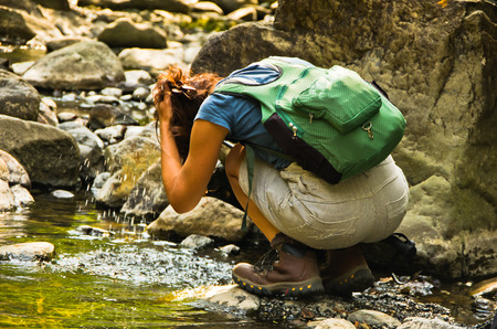 Women hiker is refreshing in a mountain stream at sunny summer day, Black river gorge, Serbia