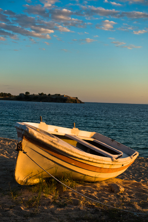 sithonia: Boat on a beach at sunset with ruins of old roman fortress in backround, Sithonia, Greece Stock Photo