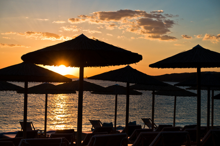 sithonia: Straw parasols on a beach at sunset in Sithonia, Greece Stock Photo