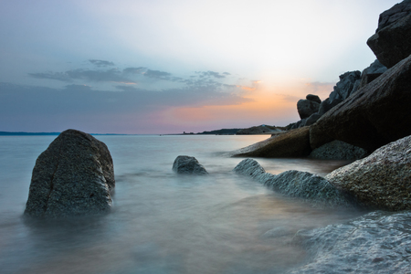 Sea rocks on a sandy beach at sunset, west coast of peninsula Sithonia, Chalkidiki, Greece