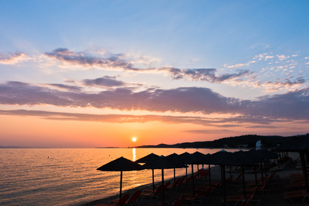 orange chairs: Sandy beach with stray sunshades and orange chairs at sunset in Sithonia, Greece Stock Photo
