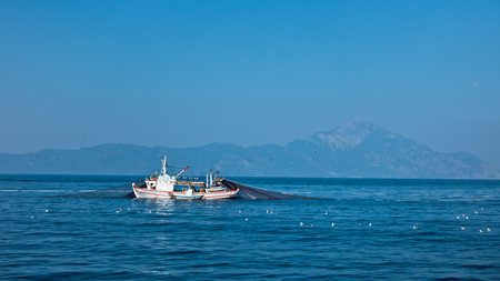 commercial fishing: Fishing boat with nests at sea in front of mountain Athos, Greece Stock Photo