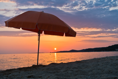 sunshade: Sandy beach with one orange sunshade at sunset in Sithonia, Greece Stock Photo