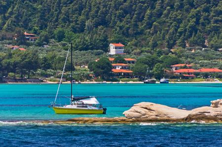 uninhabited: Sailboat at emerald green sea water at coast of small uninhabited island near coast of Sithonia, Greece