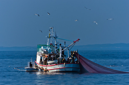 Fishing boat with nests at sea in front of mountain Athos, Greece Stock Photo