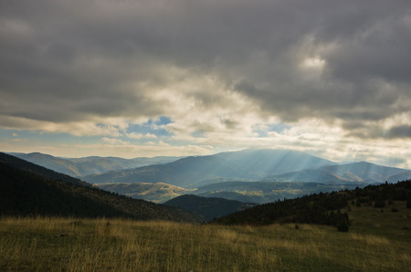Heavy overcast sky over meadows and colorful forests at autumn, mountain Goc, Serbia