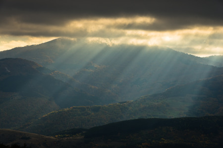 sunrays: Heavy overcast sky with sunrays over meadows and colorful forests at autumn, mountain Goc, Serbia Stock Photo