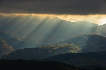 Heavy overcast sky with sunrays over meadows and colorful forests at autumn, mountain Goc, Serbia Stock Photo