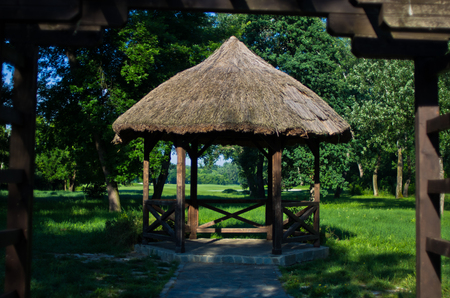 Retro looking wooden gazebo with a straw roof near golf course at Ada, Belgrade, Serbia Stock Photo