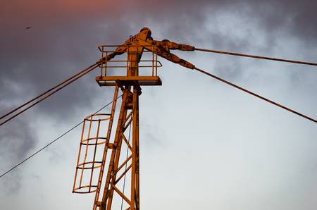 Detail of a yellow construction crane against cloudy sky at sunset in Belgrade, Serbia Stock Photo