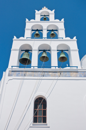 Big bell tower with 6 bells of Panagia church at Oia village at Santorini island, Greece Stock Photo