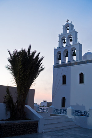 Big bell tower of Panagia church in Oia village after sunset at Santorini island, Greece