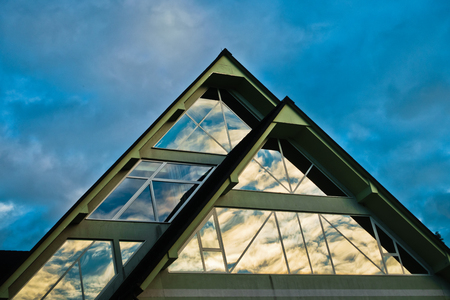 Reflection of a sky in a triangle glass shape on a building at Bled, Slovenia Stock Photo