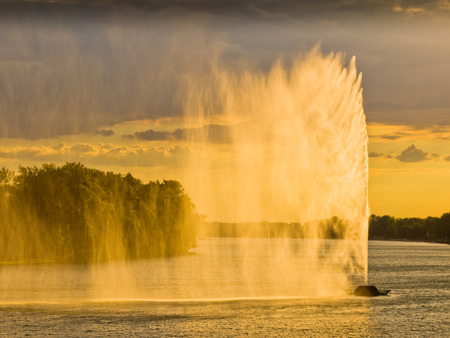 Dark clouds and strong wind create water curtain from artificial geysir against sunset light on Ada lake in Belgrade, Serbia