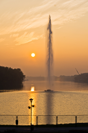 Golden reflection of a sunset on lake surface in front of artificial geysir on Ada lake in Belgrade, Serbia