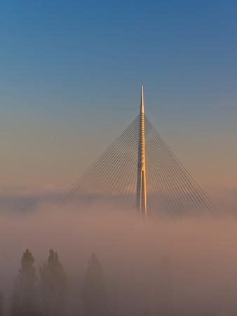 Cable bridge lit by sunshine above fog at sunrise near Ada in Belgrade, Serbia Stock Photo