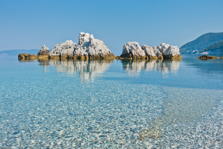 Sea rocks at calm and crystal clear turquoise water at morning, Milia beach, island of Skopelos, Greece