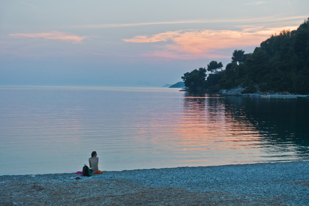 Girl sitting on a beach after sunset, Panormos bay at Skopelos island, Greece