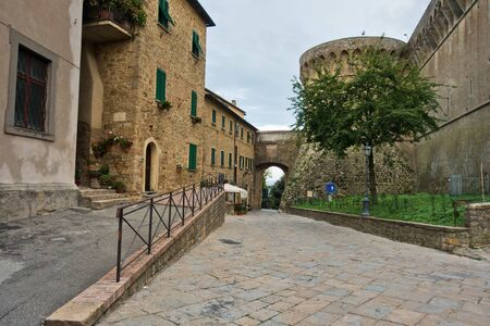 Architectural details of old houses at narrow street of Volterra with Medici fortress in background, Tuscany, Italy Banco de Imagens
