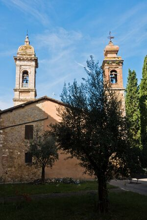 Bell towers of San Quirico church at sunny morning in San Quirico dOrcia , Siena province, Tuscany, Italy Banco de Imagens