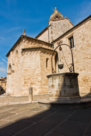 Well in front of San Quirico church at sunny morning in San Quirico dOrcia , Siena province, Tuscany, Italy