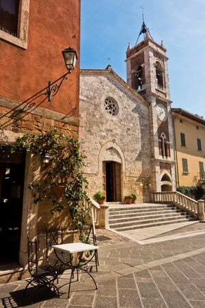 San Francesco church on main sqluare at sunny morning in San Quirico dOrcia , Siena province, Tuscany, Italy