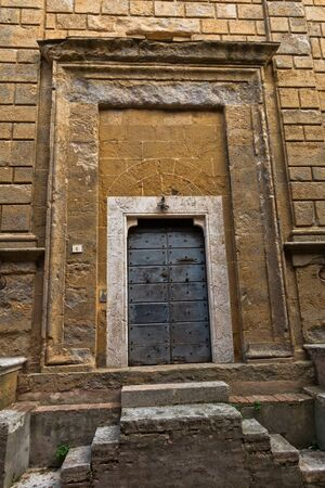 Entrance to an old church at small square in Pienza, Siena province, Tuscany, Italy