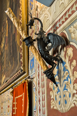 Candle stand in form of a dragon and other heraldic details inside Priori Pallace in Volterra, which is the oldest city council hall in Tuscany, Italy