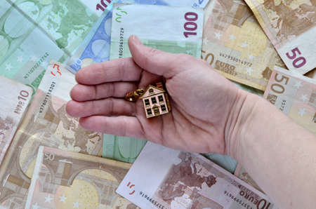 Money as a background and a hand holding a small house photo