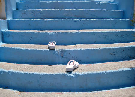 metaphysical: Flip-flops walking up the stairs. The scene has been shot on a windy beach of Rhodes island, in a hot sunny day.