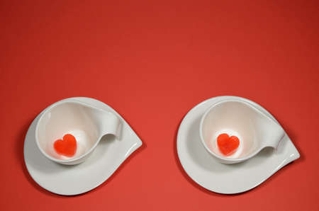 ice cubes: Two cups with heart ice cubes on red background Stock Photo