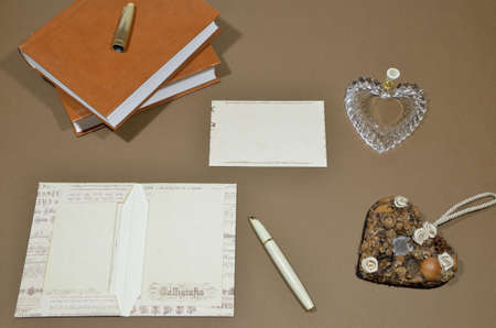 fine print: Set of letters, pen, penholder heart shaped, heart and books on a brown background. Stock Photo