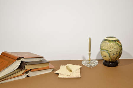 pen holder: Set of letters, pen holder heart shaped, pen, small globe and books on brown backgound