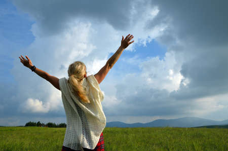 joy: Happy and joyful woman spreading hands to the sky and showing love for nature