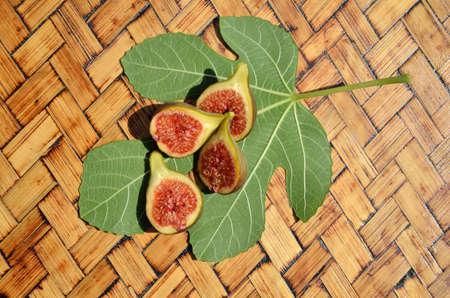 fig leaf: Figs halves on fig leaf set on wooden table Stock Photo