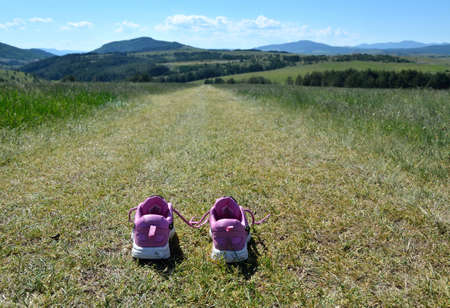 off path: Sneakers on grass mountain road to hills and valleys Stock Photo